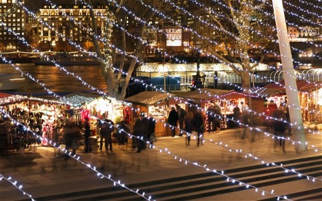 View of the traditional Christmas Market along the South Bank Queen's Walk  London at night looking through Xmas lights